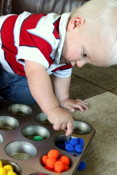 We love simple fine motor play by sorting pom poms for toddlers