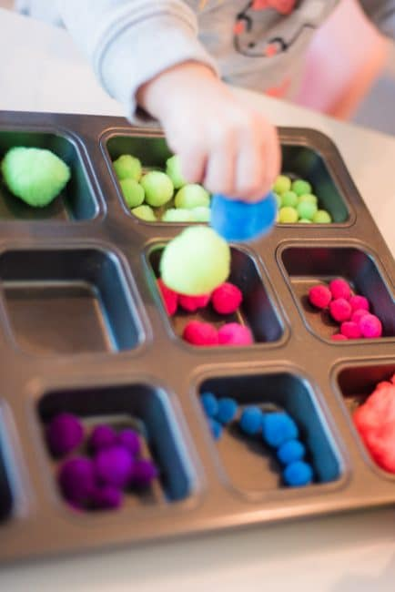 This simple toddler fine motor skills activity only needs pom poms and a muffin tin to sort them.