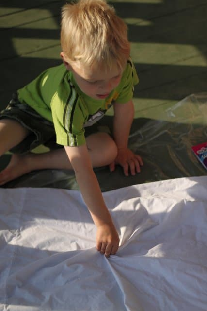 Help your child set up their pillowcase to tie-dye