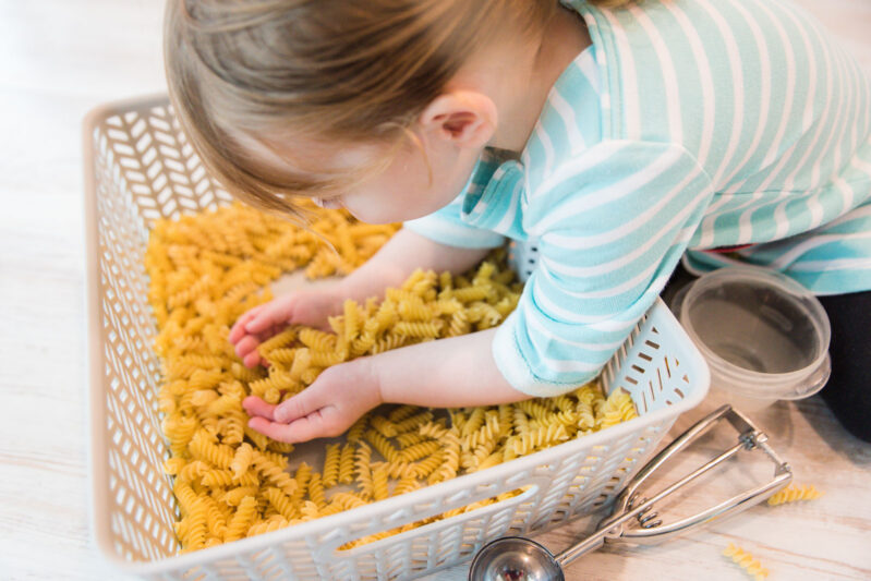 Pasta noodles make for a great sensory bin play time for toddlers and preschoolers.