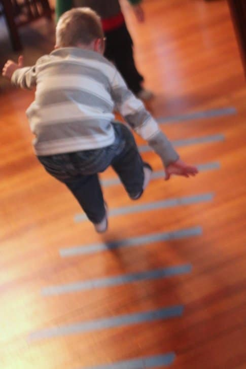 Burn off indoor energy with a simple tape jumping game to work on preschool gross motor skills!