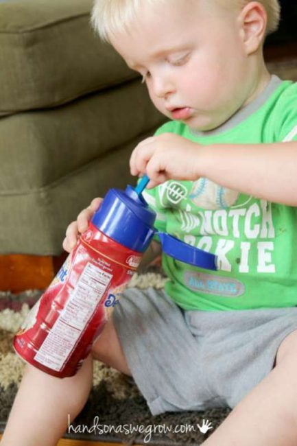 A fine motor activity for toddlers to do with a plastic bottle