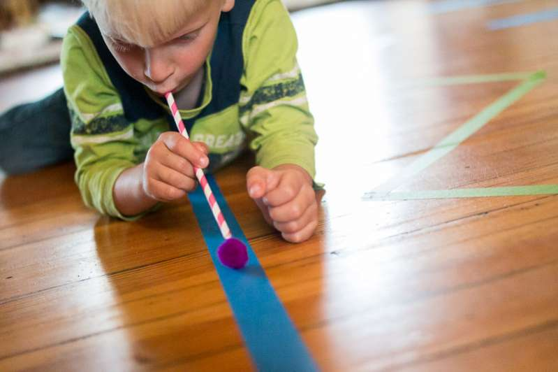 Work on breath control as you blow pom poms along lines of colored tape