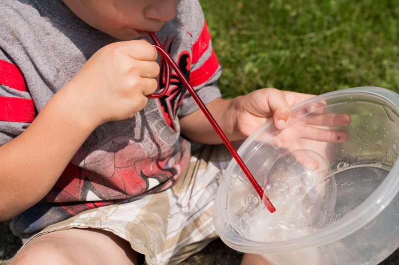 Blowing bubbles with a homemade bubble solution - one of 10 hands-on science & math activities for the kids to LOVE!
