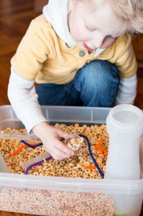 A simple cereal sensory bin for toddlers with threading activity