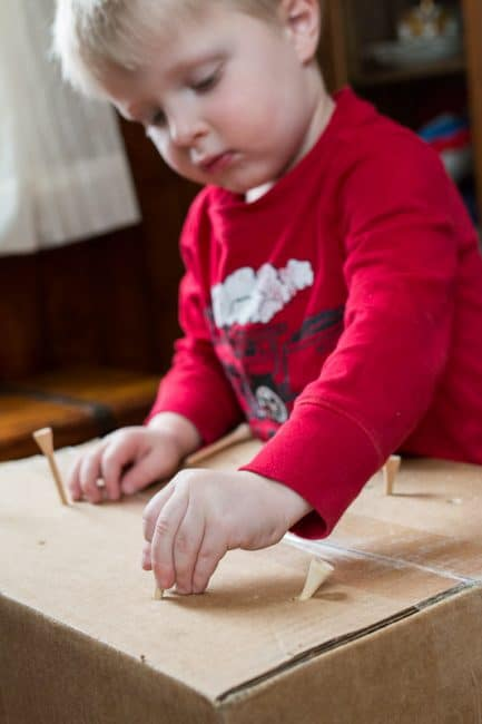Poking tees into a cardboard box - great idea for fine motor skills for toddlers