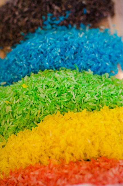 A rainbow rice sensory bin is great for toddlers! Learn how to make colored rice like this.