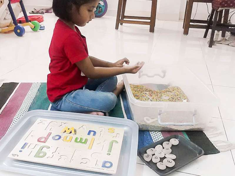 Matching letters in a rainbow rice sensory bin