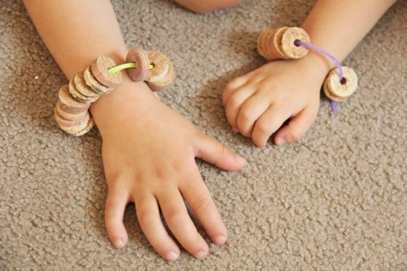 Cork bead bracelets can help kids develop and build fine motor skills like threading.