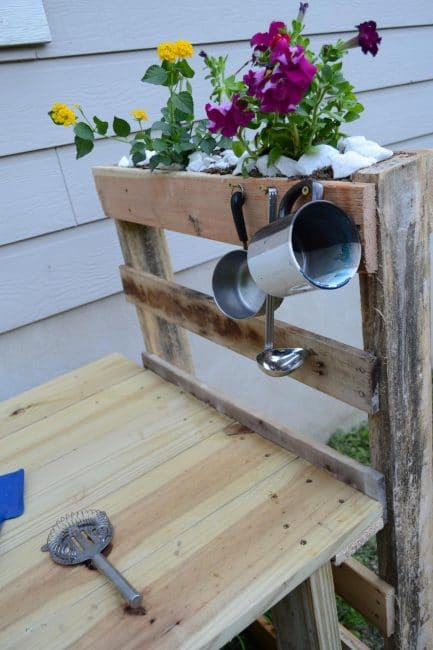 Use nails or hooks to hang cooking utensils on the mud kitchen