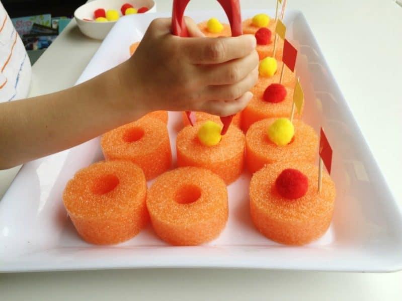 Use big tweezers to balance pom poms on sliced pool noodles