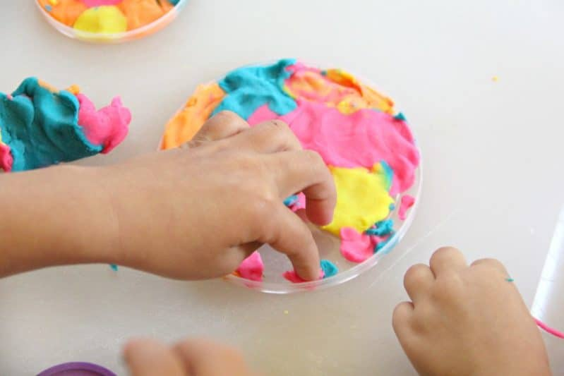 Use play dough and a recycled plastic lid to make a stunning play dough suncatcher craft with the kids!