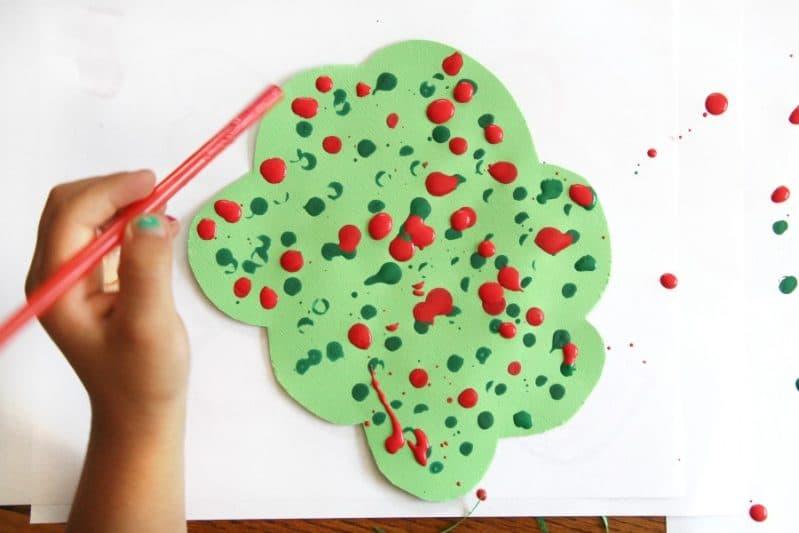 Create a straw drop painting apple tree craft to work on fine motor skills.