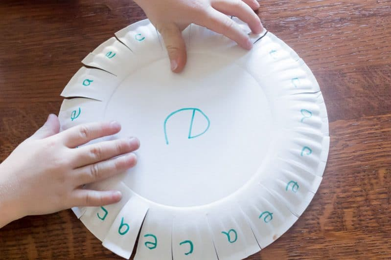 Using a paper plate to practice learning a couple of letters -- so smart!