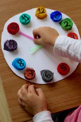 Upcycle old bottle caps to make this color matching clock for preschoolers.