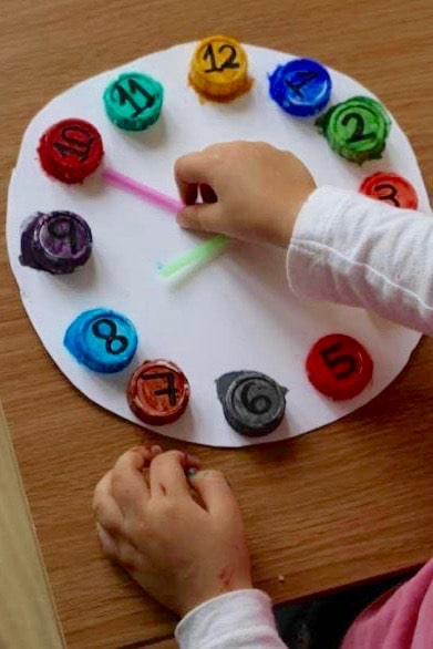 Old bottle caps make this upcycled clock for a color matching clock for preschoolers.