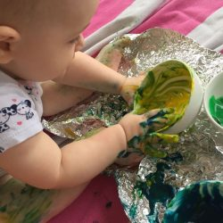 This baby foil painting art activity is messy, but so much fun! Learn how to make instant edible finger paint to make painting on foil safe for you baby.