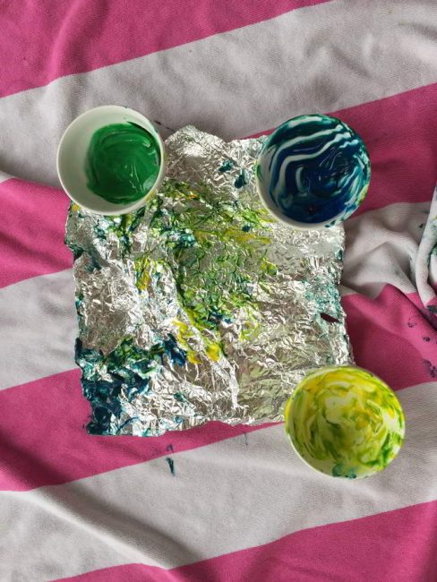 This baby foil painting art activity is messy, but so much fun! Learn how to make instant edible finger paint that's safe for your baby.