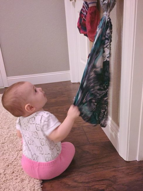 Try this simple baby scarf pull activity to get your baby moving! Encourage gross motor skills with this low-prep baby play idea.