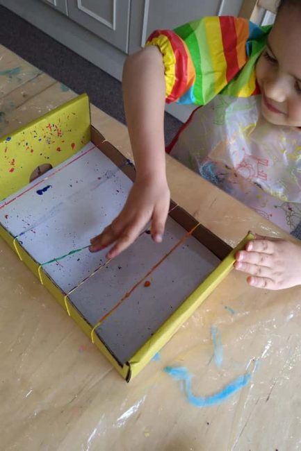 Your preschooler will love creating beautiful artwork with rubber bands and paint!