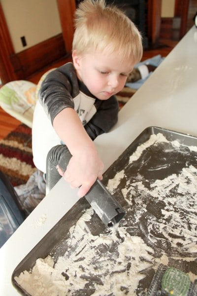 Suck up the flour sensory play with a vacuum to make cleaning fun for kids!