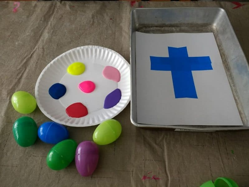 Try a fun Easter egg painting activity to make a tape resist cross with your kids!