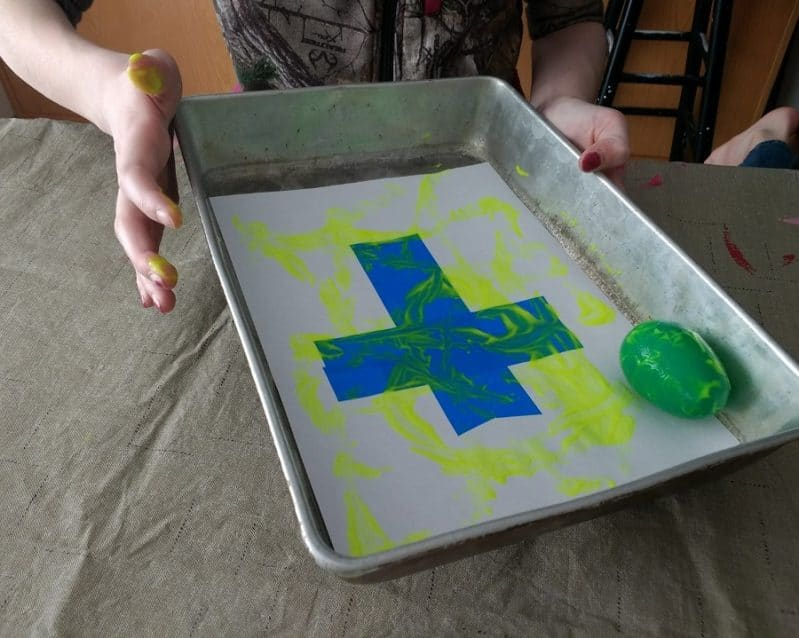 Roll and paint a tape resist cross using plastic Easter eggs!