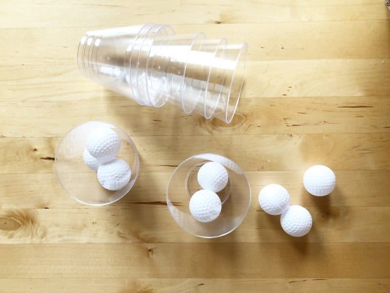 Grab some light weight balls and some cups to set up a fun gross motor challenge for your kids!