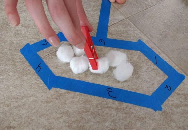 Move cotton balls into each shape using a clothespin