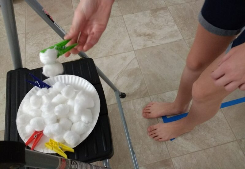 Challenge your kids to the cotton ball transfer activity to work on gross and fine motor skills!
