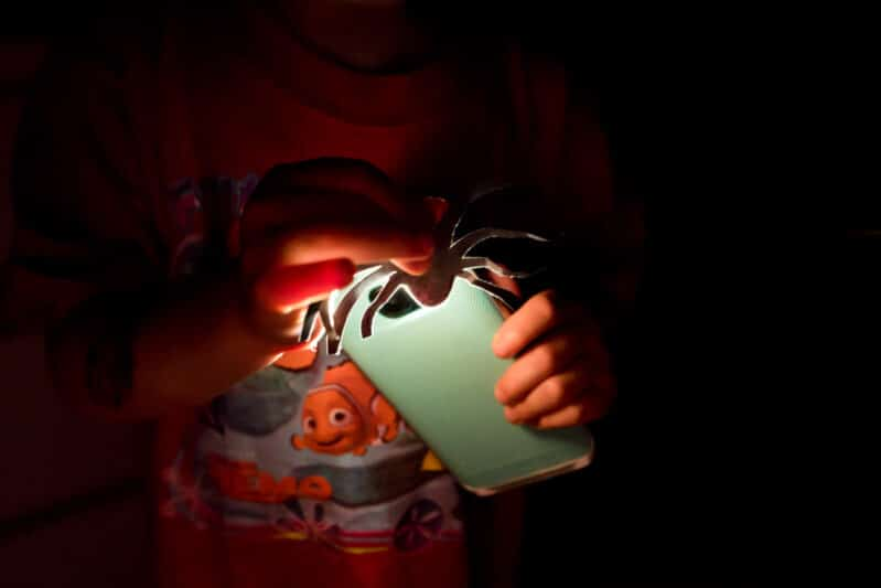 """Search for """"spiders"""" using flashlights in a fun Halloween scavenger hunt!"""