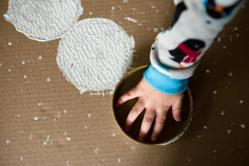 Upcycle a box into a snowman painting project for kids! Stamp down snowballs!