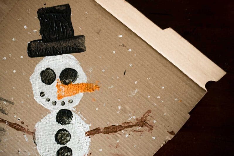 Upcycle a pizza box into a wintery snowman painting project for kids!