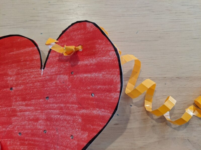 Thread ribbons through the heart for a fun fine motor craft for kids