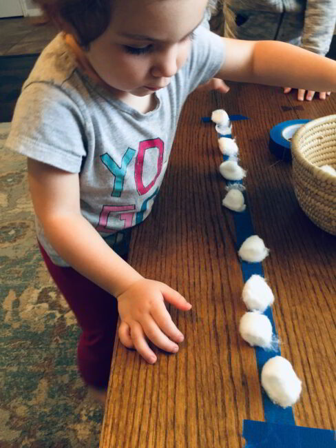 Count and squish on a fun cotton ball lineup game for toddlers!