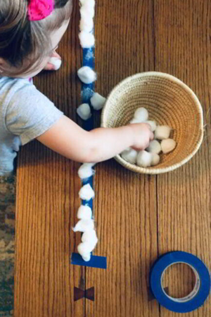 Work on fine motor skills with a quick cotton ball lineup for your toddler.
