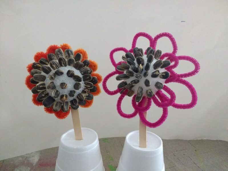super simple pipe cleaner flowers for preschooler to make with sunflower seed centers -- a fun spring flower craft!