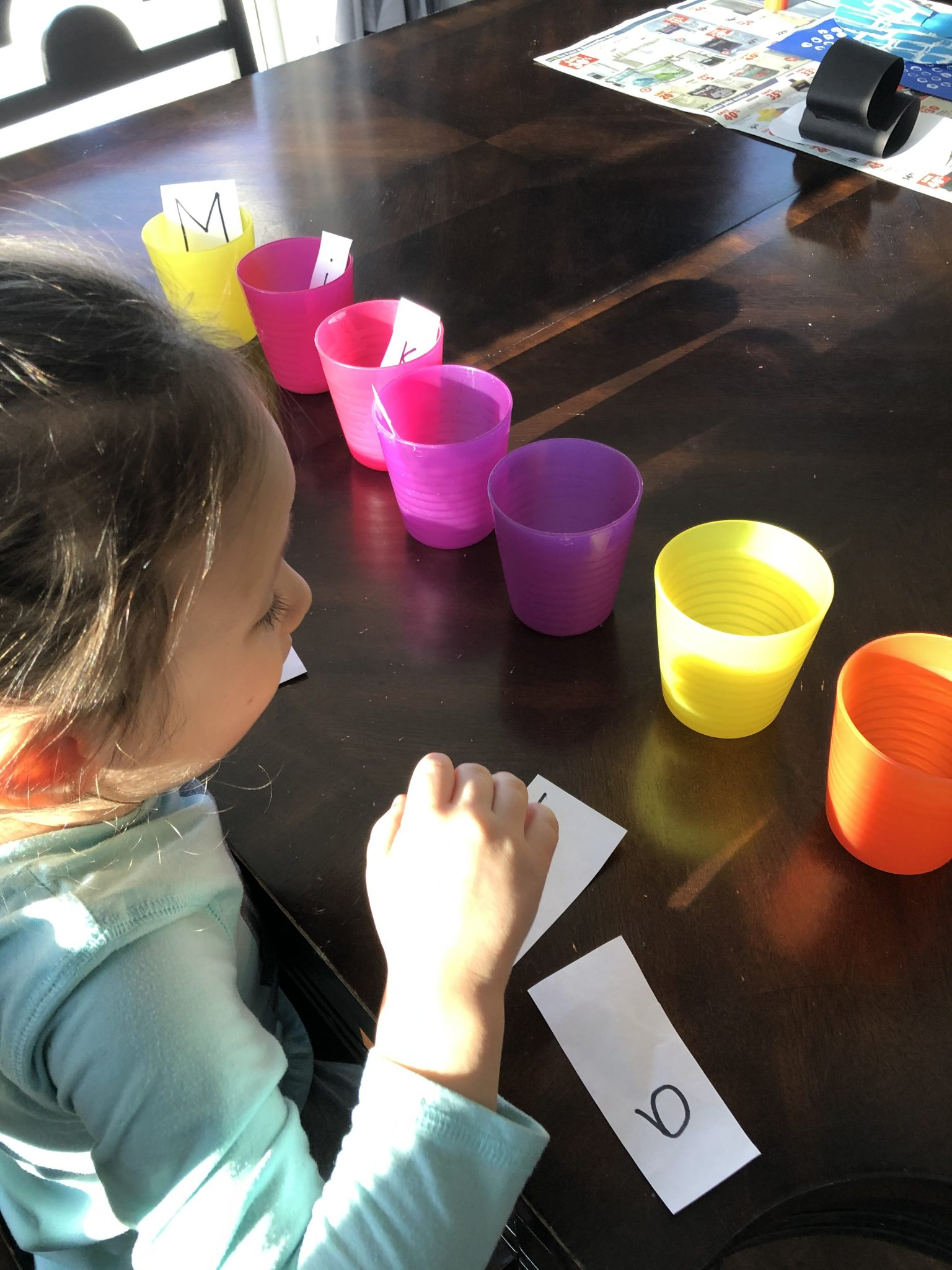 Putting the letters of your child's name into cups.