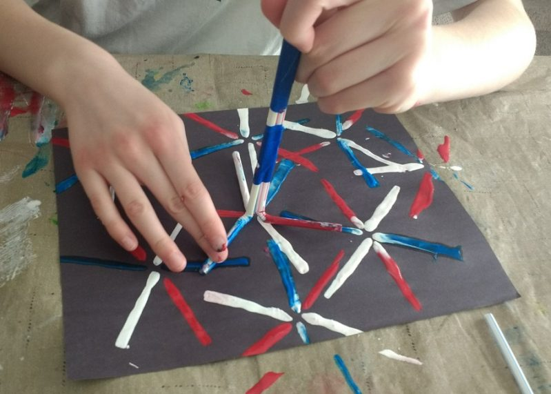 Painting fireworks using straws to stamp