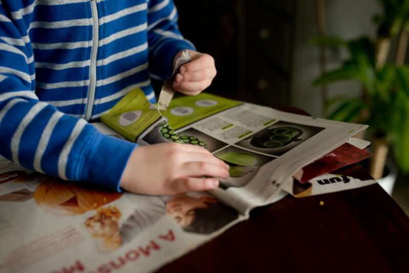 Tearing paper while going on a magazine scavenger hunt - a fine motor activity for preschoolers.