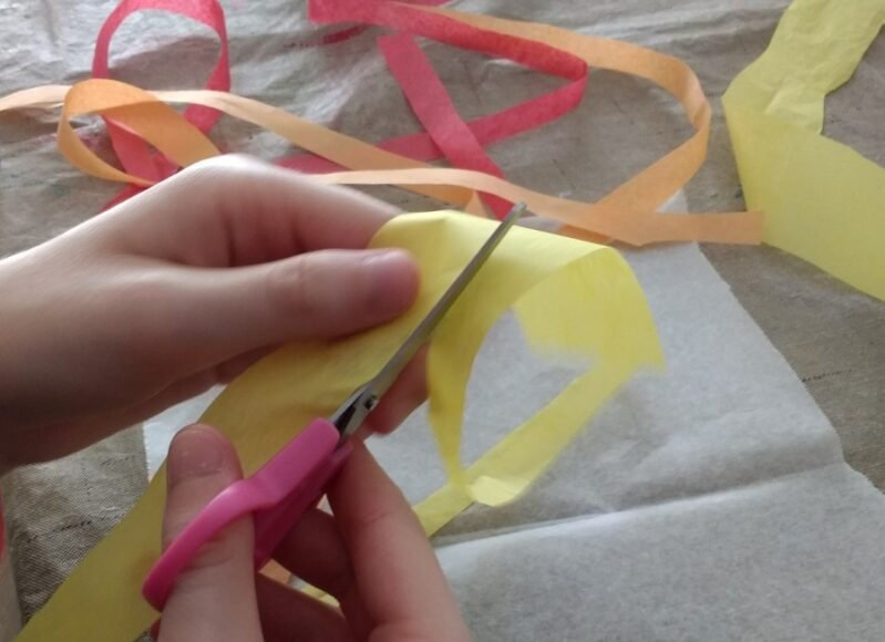 Cutting up tissue paper for leaf suncatcher craft for kids.