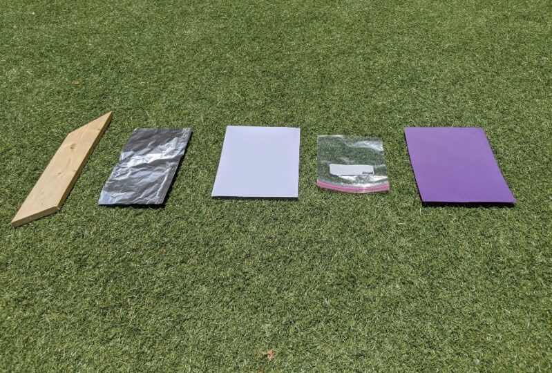 Surfaces set up for seeing what makes ice cubes melt faster in the sun.