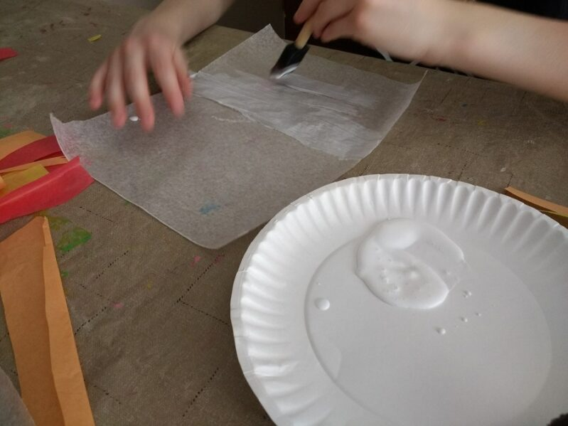 Painting glue on wax paper for leaf suncatcher craft for kids.