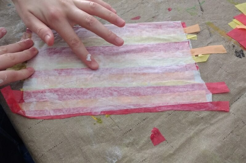 Gluing tissue paper between wax paper for easy fall leaf suncatcher craft for kids.