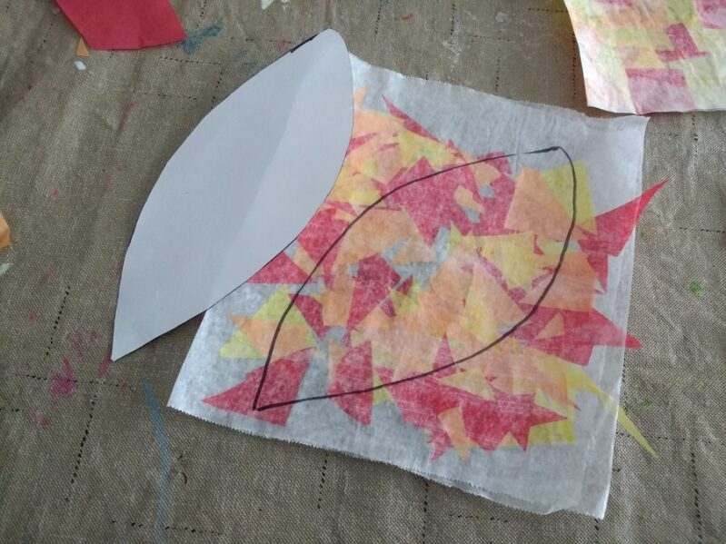 Cutting out the tissue paper leaf for suncatcher craft.