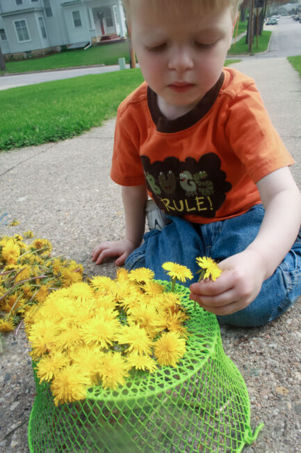 Outdoor play: Threading dandelions into a basket to make a hat.