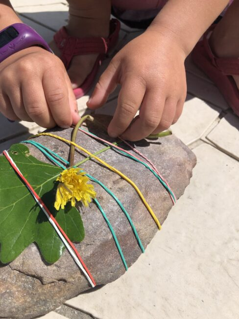 Find nature items to weave into the elastics on your rock