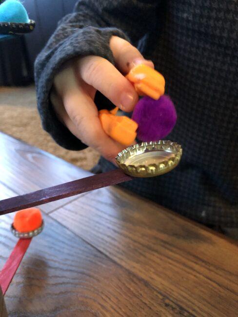 Use tweezers to place pom pom on the balance tree.