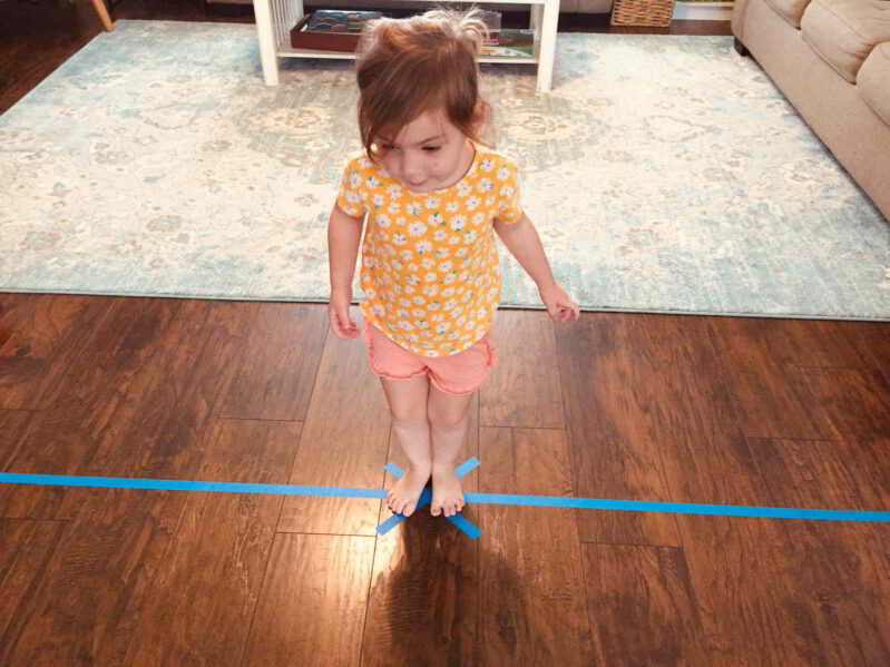 Try this fun balance beam toddler game to match colors and develop gross motor skills!