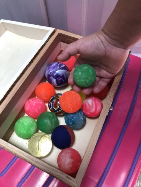 Bouncy balls are great for gross motor play. Try this bouncy ball game at home!